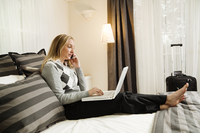 Business woman in hotel room talking on phone using computer