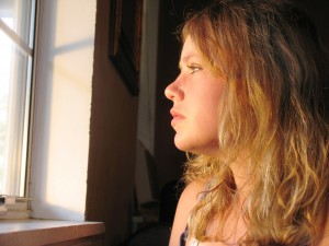 image of girl looking out window thinking about new ideas for brain resistance post - Delightability