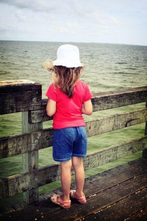 girl on pier looking onward - Robots Don't Kill Jobs But CEOs Do - Delightability blog